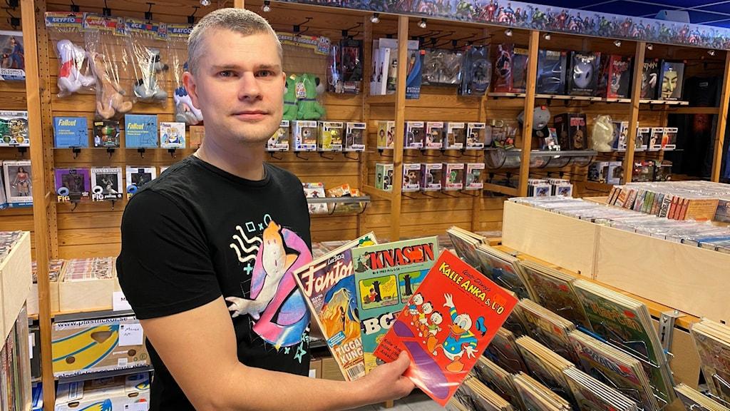 Man med svart t-shirt som håller i serietidningar inne i en butik.