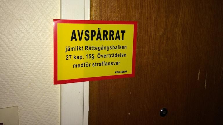 En dörr avspärrad av polisen. Foto: Per Larsson/Sveriges Radio.