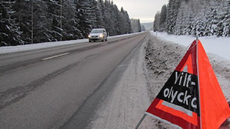 Skogskantad väg med bil som kommer åkandes. Ett orange trafikvarningsmärke med texten viltolycka. Färre viltvarningsskyltar. Foto: Lennart Nordenstein/SR Värmland.