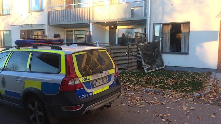 En polisbil framför en brandskadad lägenhet