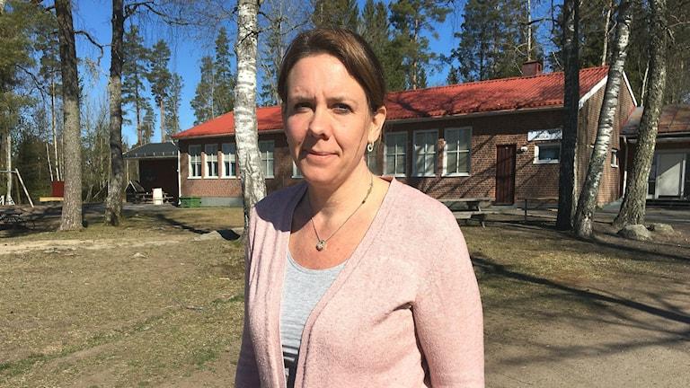 Therese Arvholm, ordförande för Skruvstads föräldraförening. I bakgrunden skymtar Skruvstads skola, med flera träd på gården. Foto: Magnus Hermansson/Sveriges Radio.