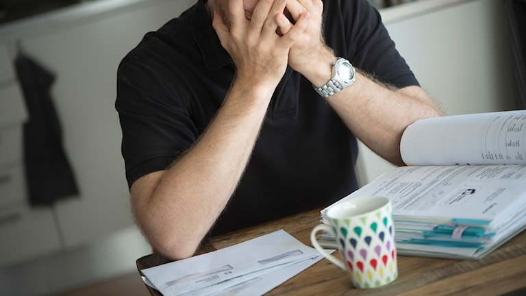 En person med räkningar på bordet. Foto: Fredrik Sandberg/TT.