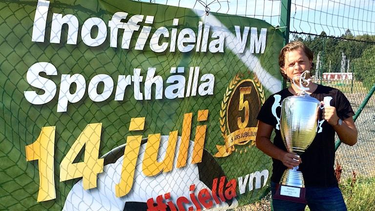 Ludwig Milton med en stor pokal framför det inoffciella fotbolls-VM:ets banderoll.