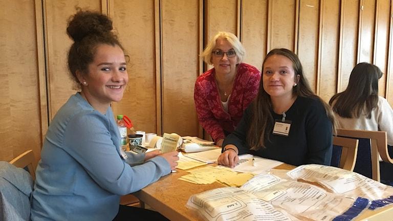Tre kvinnor sitter kring ett bord med röstlappar