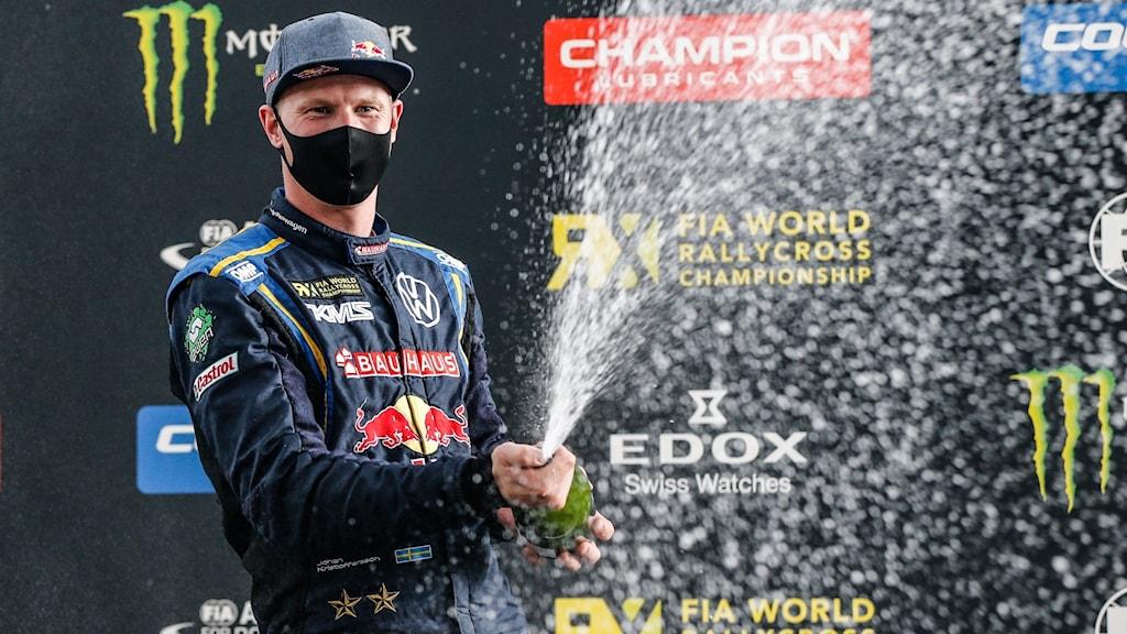 Johan Kristoffersson firar en rallycrosseger, iklädd svart munskydd, och en sprutande flaska bubbel i händerna. Foto: Tom Banks/FIA World rallycross championship.