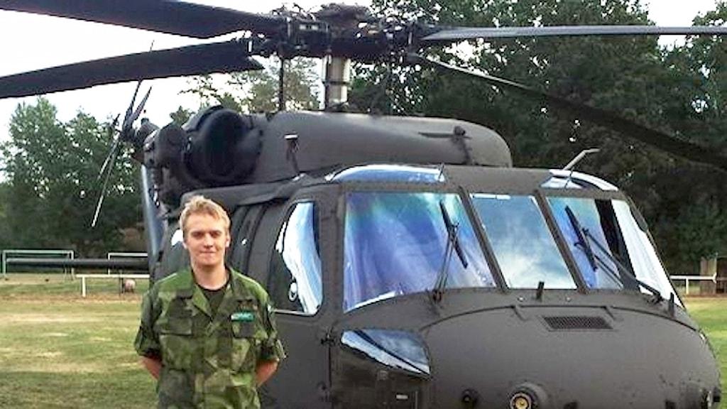Man i grönkläder framför helikopter