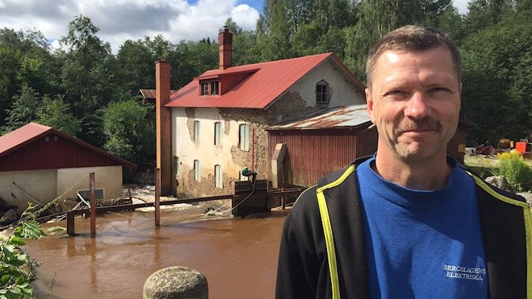 En man, Hans Åke Karlsson står framför dammen som tidigare varit översvämmad. FOTO: Elias Andersson