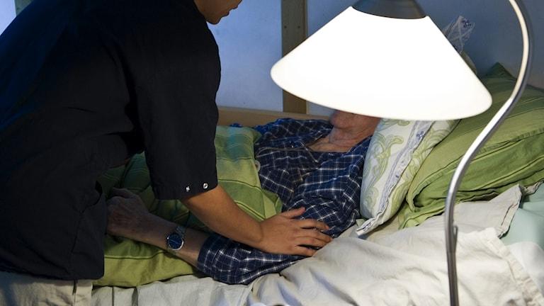 En äldre kvinna ligger i en säng, hemtjänsten besöker. Foto: Henrik Montgomery/TT.