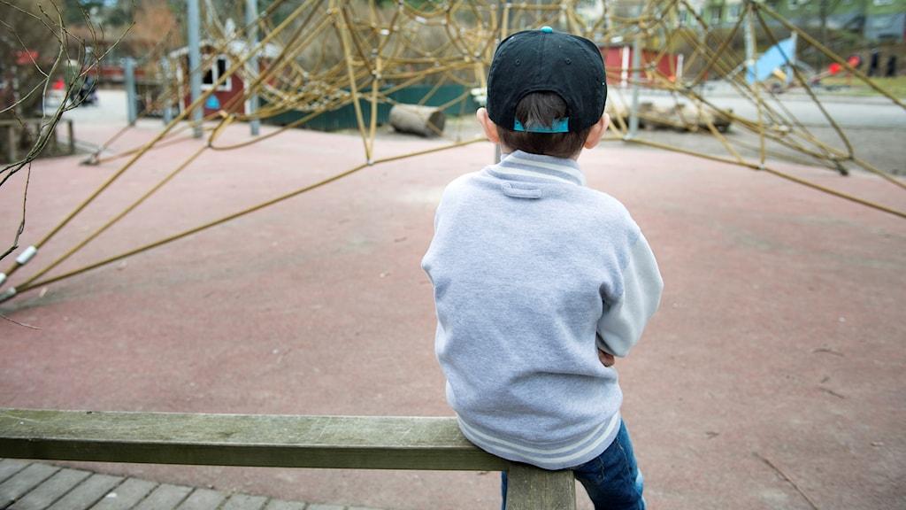 Ett ensamt barn vid en lekpark.
