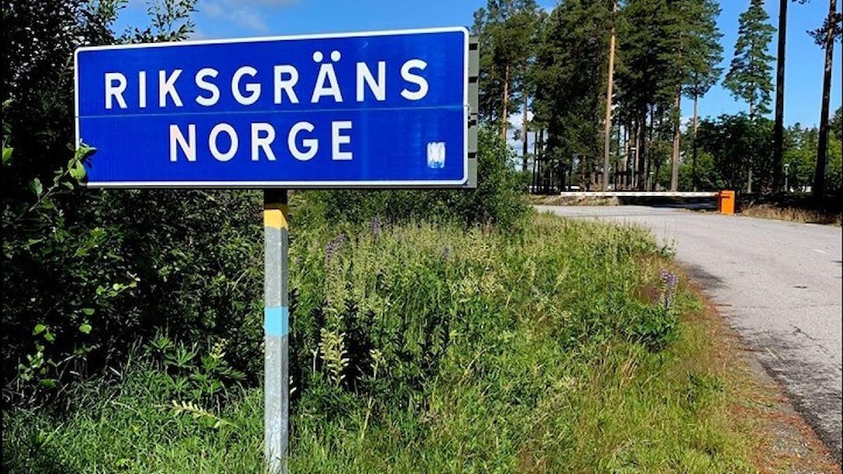 en skylt och en vägbom markerar gränsen mellan sverige och norge