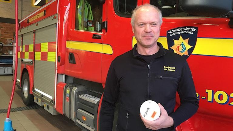 Ola Åkesson med en brandvarnare i handen. Foto: Jonas Berglund/Sveriges Radio.