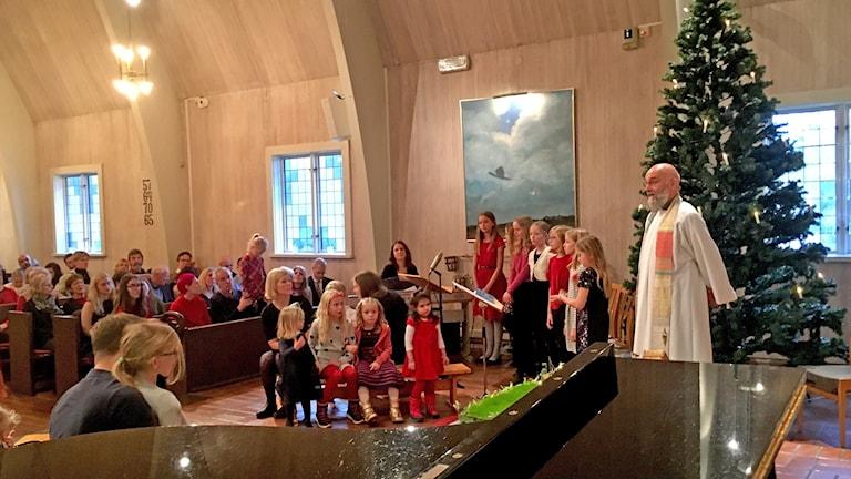 församling, präst och barnkör vid julfirande