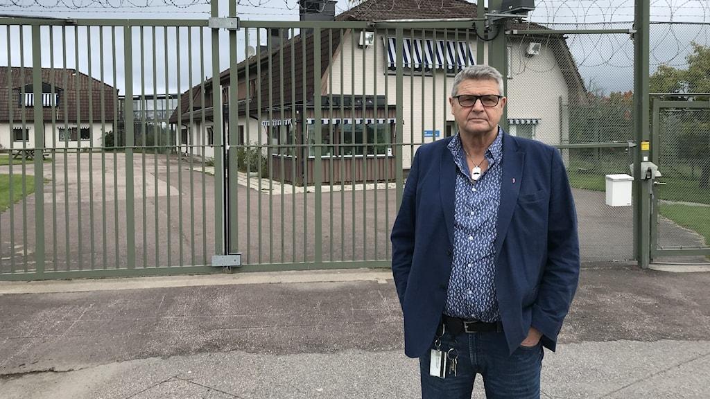 En man står framför grindarna till ett ungdomshem.