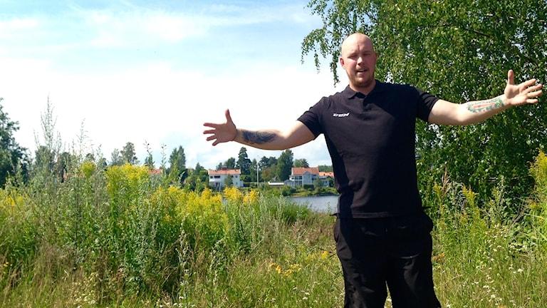En bild på Mattias Eppeline när han måttar överdrivet med armarna storleken på en fisk