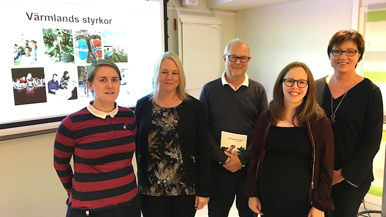 Fem personer framför en presentationsbild.