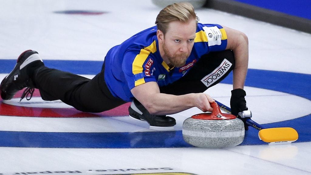 Niklas Edin är på väg att släppa sitt curlingsten på isen. Foto: Jeff McIntosh/AP