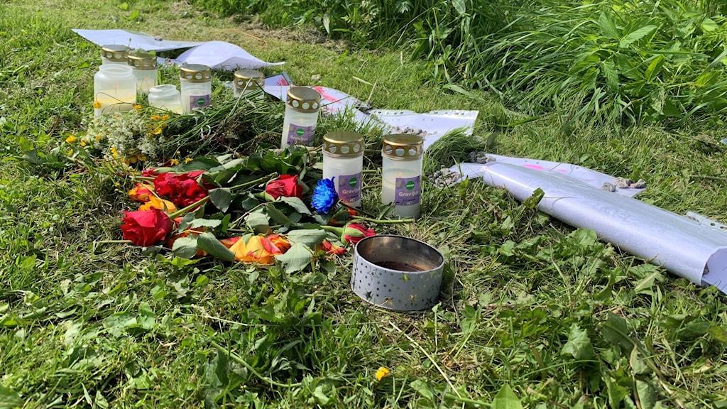 Blommor och gravljus på marken.