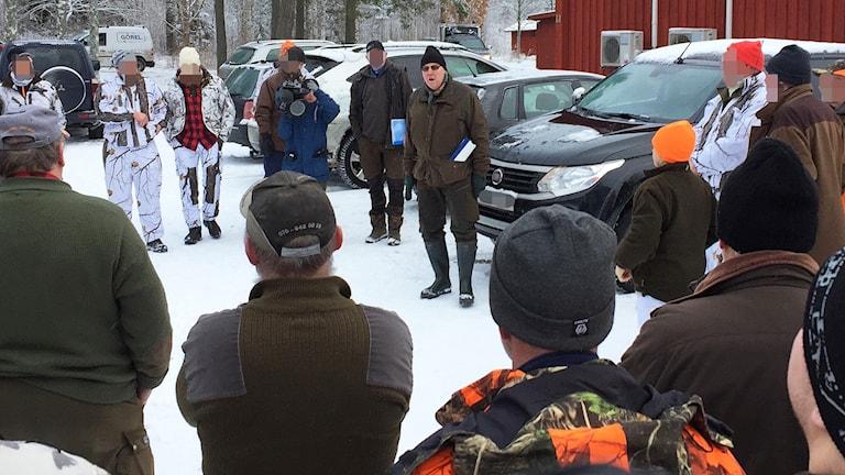 Jaktledare informerar jägare vid en uppsamlignsplats. Foto: Robert Ojala/Sveriges Radio.