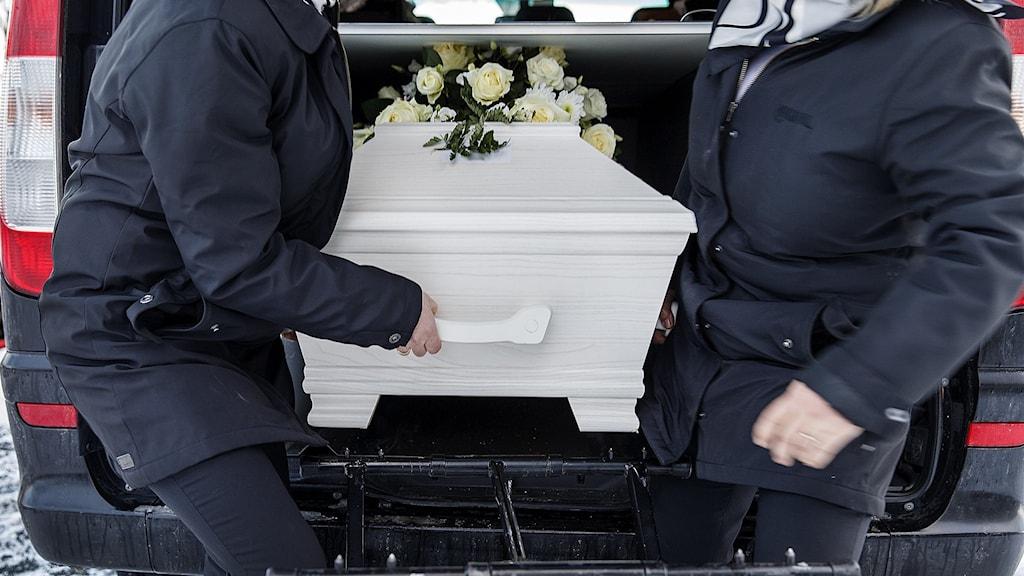 Två män lyfter ut en kista ur en bil.
