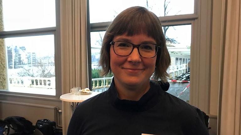 En kvinna med brunt page och glasögon tittar in i kameran