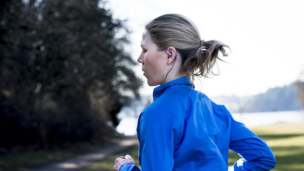 Kvinna i blå jacka springer med hörlurar i öronen. Foto: Nora Lorek / TT.