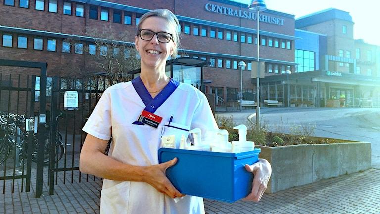 Susanna Sandberg håller i en låda full med olika handkrämer. Foto: Jonas Berglund/Sveriges Radio.