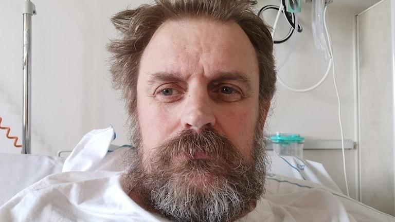 man i sjukhussäng med mycket skägg