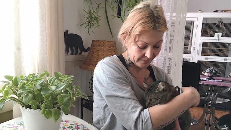 Camilla Strömberg gosar med en katt. Foto: Jenny Tibblin/Sveriges Radio.