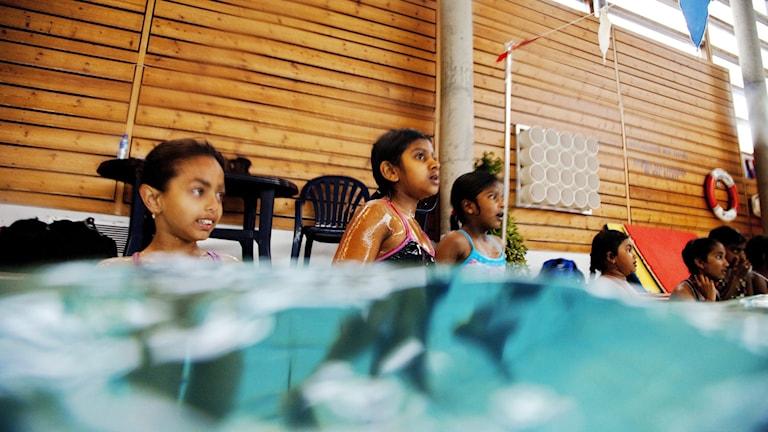 Barn som är i bassäng för simskola.