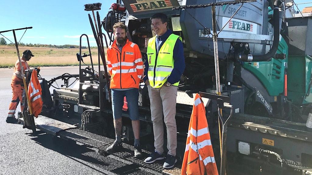 David Jansson och Lars Ogenvall står framför asfaltsmaskinen. Foto: Mats Fagerström/Sveriges Radio