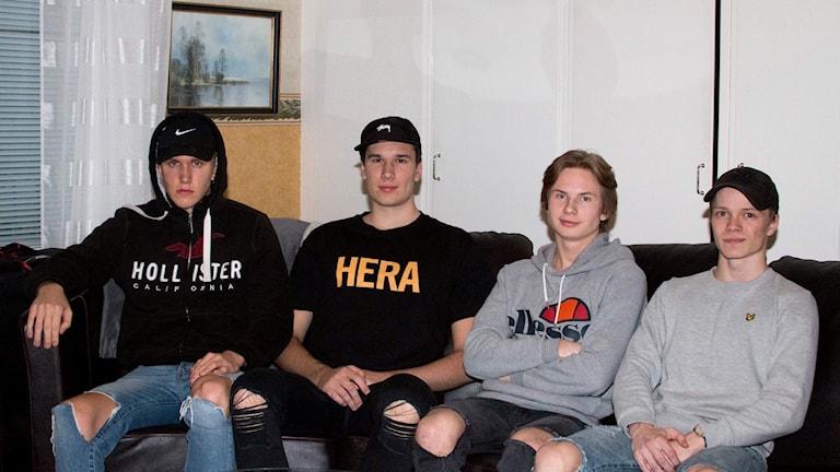 Fyra unga män runt 20 år sitter i en soffa.