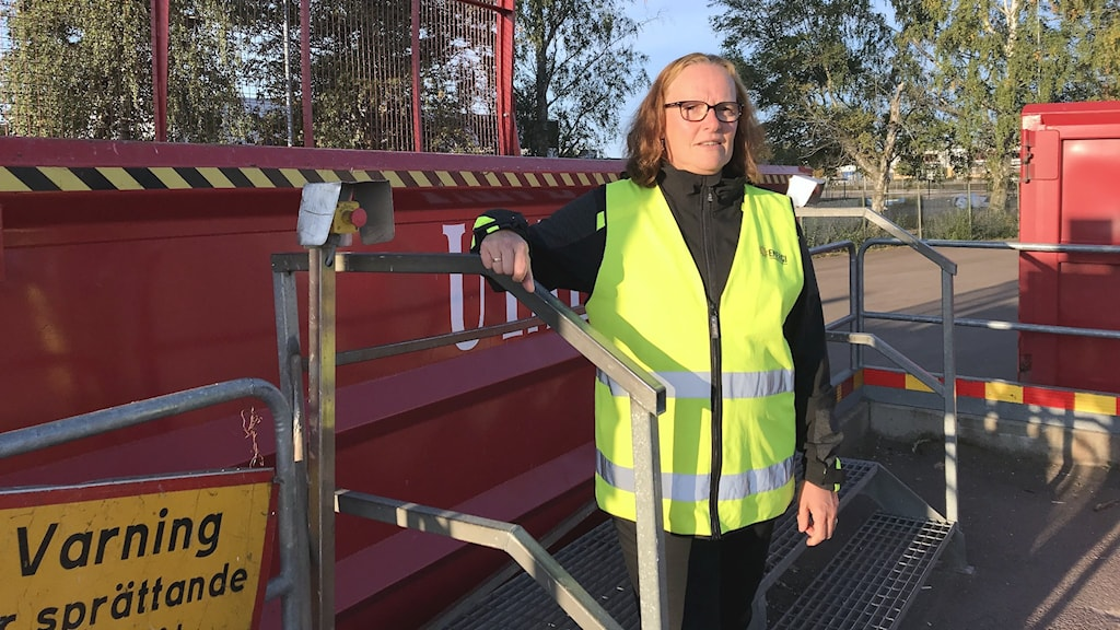 Ann-Louise Olofsson står vid en sopcontainer. Foto: Per Larsson/Sveriges Radio.