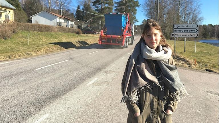 Emma Borgstrand, vid vägen genom Värmskog. En lastbil kör förbi. Foto: Magnus Hermansson/Sveriges Radio.