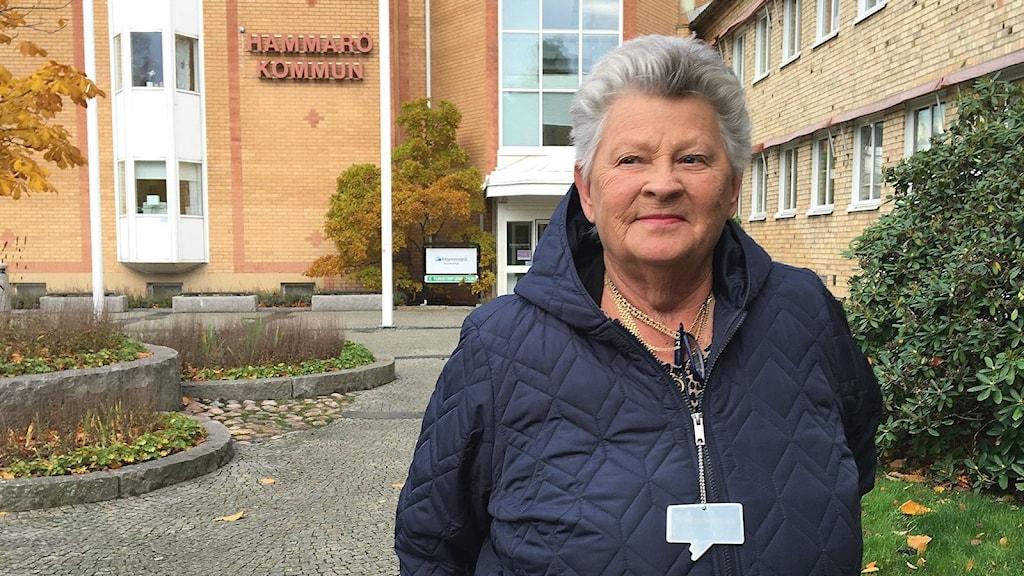 Margareta Ivarsson, centerpartistisk kommunpolitiker, iklädd blå jacka. I bakgrunden syns fasaden till Hammarö kommunhus. Foto: Magnus Hermansson/Sveriges Radio.
