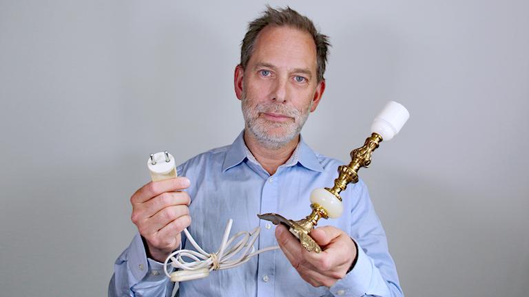 Per Samuelsson håller i en gammal lampa med tillhörande kontakt. Foto: Lars-Gunnar Olsson/Sveriges Radio.