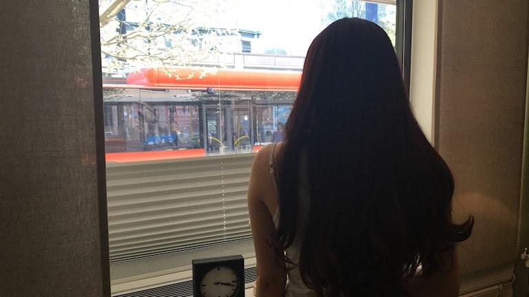 Flicka med mörkt hår framför fönster. Foto: Sveriges Radio.