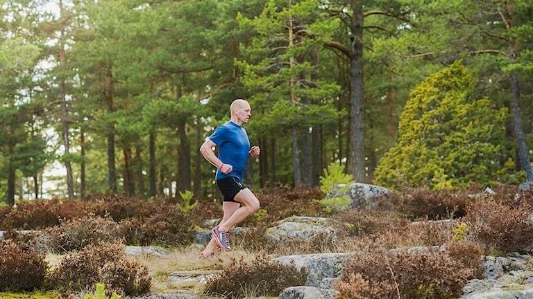 En man i blå t-shirt som löper ute i skogen