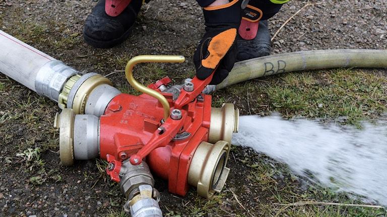 En brandman släpper ut vatten ur en grenkopping ( kyrka ) vid en brand