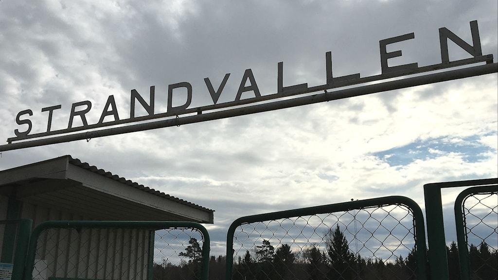 Skylten vid entrén till Strandvallen i Mallbacken, mot en molnig himmel. Foto: Magnus Hermansson/Sveriges Radio.