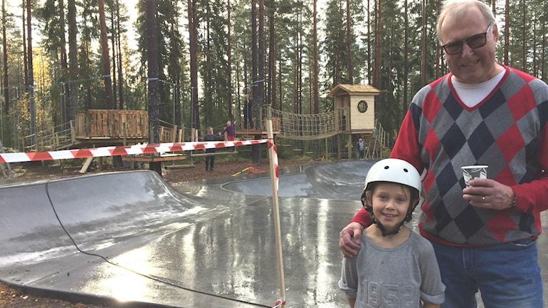 Man och ung pojke står framför en aktivitetspark i skogen.