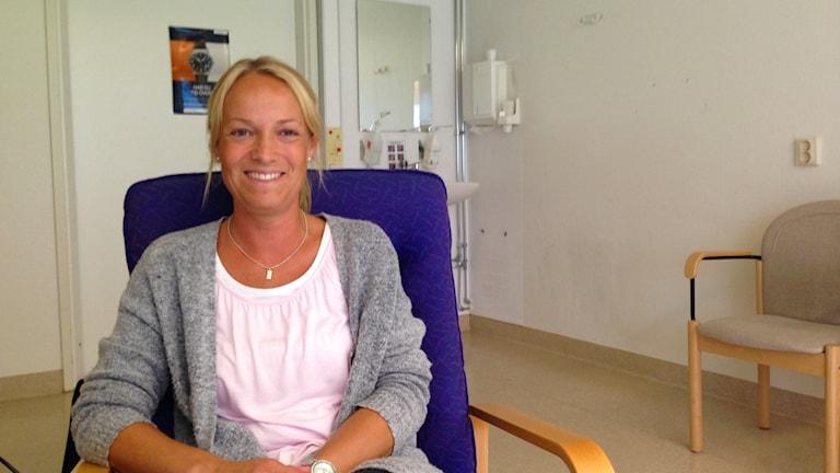 Anna-Karin Ring ler i en stol.