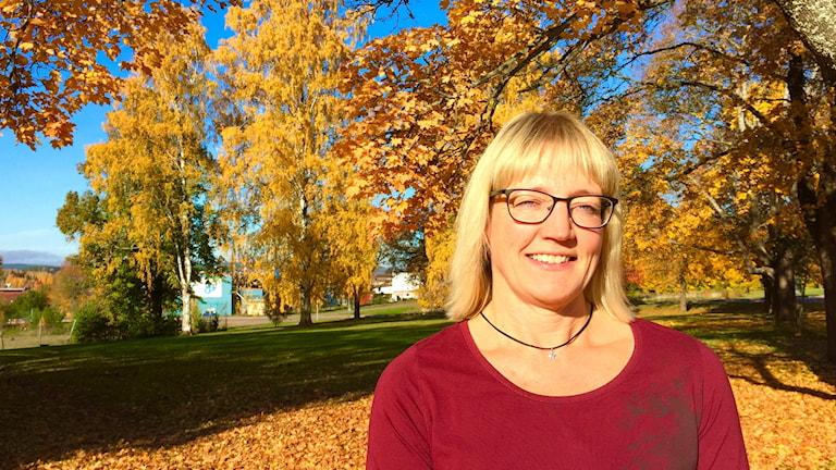 Carina Carlsson i en park med höstklädda träd. Foto: Amanda Moln/ Sveirges Radio.