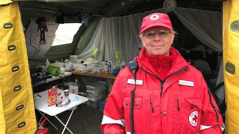 Helene Hjalmarsson på Röda korset står framför ett tält. Hon har på sig röda kläder från organisationen. Foto: Per Larsson/Sveriges Radio.