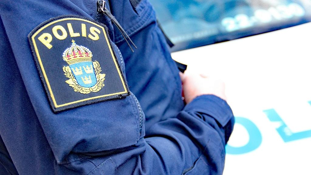 En polismans arm med polismärket på ärmen. Foto: Lars-Gunnar Olsson/Sveriges Radio.