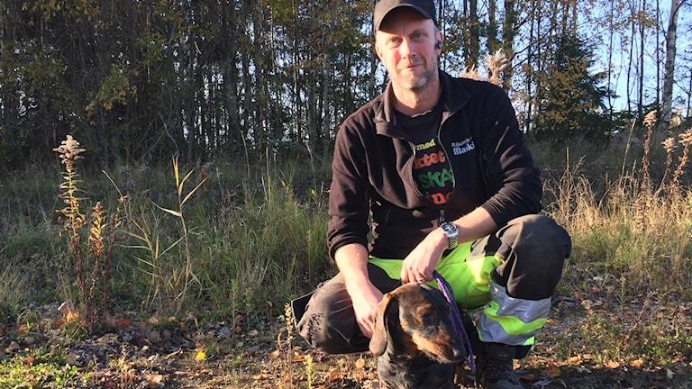 En man står knästående med sin hund, en tax, framför sig. I bakgrunden höstgula träd.