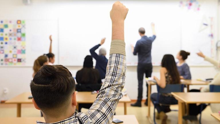 Pojke räcker upp handen i klassrum