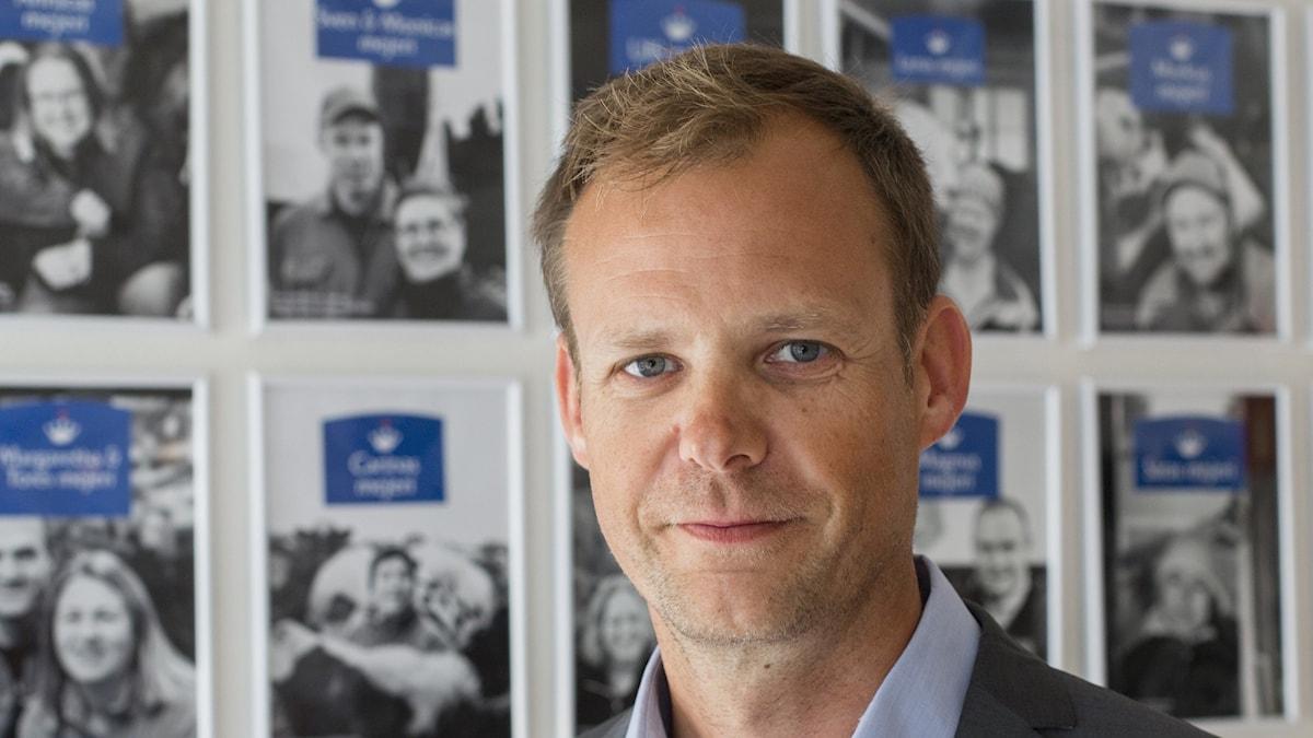 Anders Fredriksson står framför en vägg med svartvita bilder. Foto: Jan Lindmark/Norrmejerier.