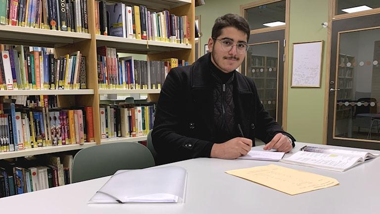 Abbas Hosin sittandes vid ett bord. Foto: Jonas Berglund/Sveriges Radio.
