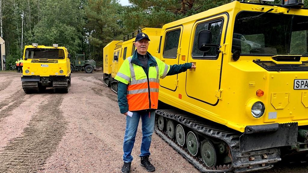 man står bredvid gul liten bandvagn