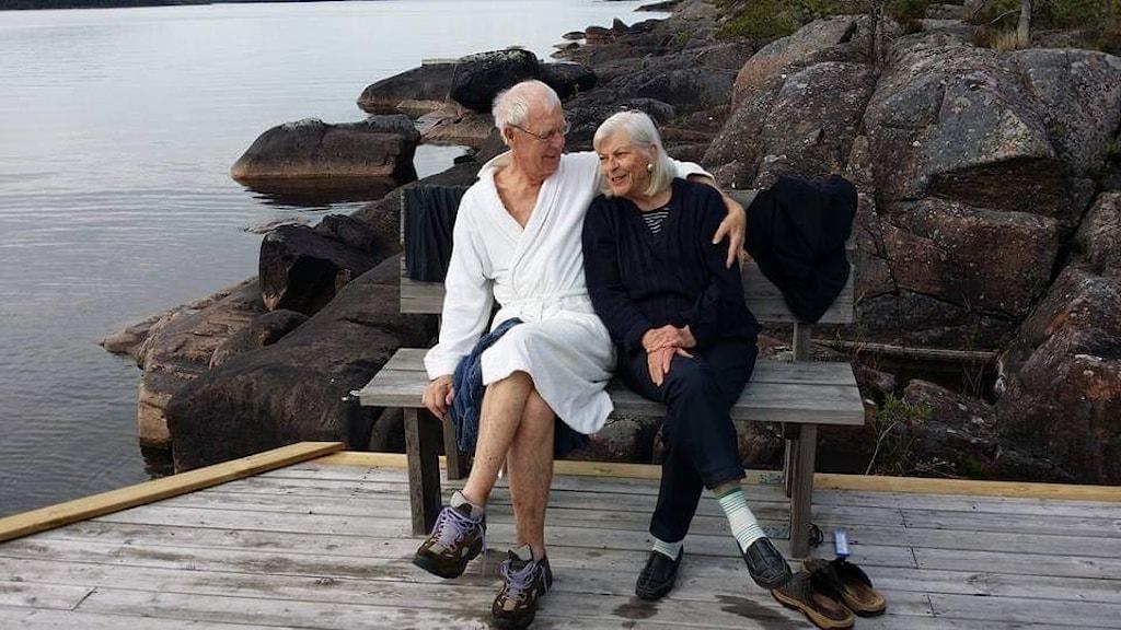 Carl Scheffer sitter med sin fru Helena på en bänk vid vattnet.